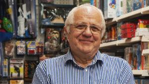 Äldre man i glasögon och smårutig skjorta står i affär omgärdad av leksaker.