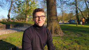 Eddie Björklöf sitter i en park i solen.