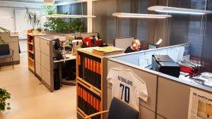Bild av kontorsutrymme med flera avskärmade skrivbord.