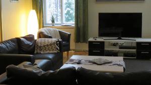 Ett vardagsrum med svarta lädersoffor och en tv. Plädar på stol och soffa och stearinljus på soffbordet. en tavla på väggen.