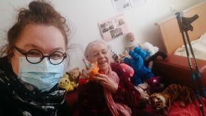 silmälasipäinen tytär maski päällä ja vanha äiti sohvalla selfie hoivakodissa