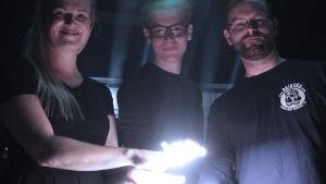 Marianna Jakobsson, Klaus Mäkelä ja Pessi Levanto kädet valonheittimessä.