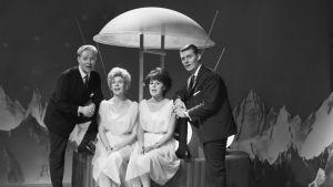 Eino Virtanen, Brita Koivunen, Pirkko Mannola ja Esa Laukka laulavat satelliittia muistuttavan laitteen äärellä Karuselli-ohjelmassa 1964.