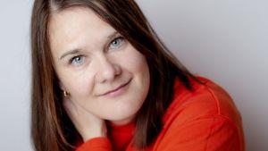 Porträttbild av Marie Aubert som tittar rakt in i kameran, iklädd en orange tröja.