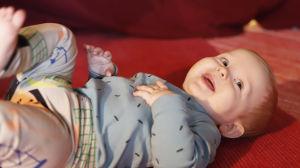 Soiva syli: lapsi makaa lattialla