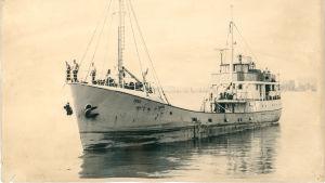 Sepiafärgad bild på skeppet MS Irma som försvann 1968. Folk på däcket på den 45 meter långa järnskepet.