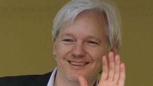 Julian Assange vinkar till sina anhängare genom ett fönster på Ecuadors ambassad 16.6.2013