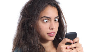 Kvinna med rufsigt hår och stirrig blick ser på telefon