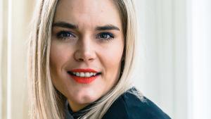 Marja Kihlström katsoo valoisassa kuvassa hymyillen kameraan.
