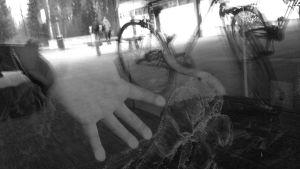 hand mot fönsterglas med reflektion av skolgård och cyklar