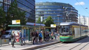 Bilden visar en spårvagn och en spårvagnshållplats.