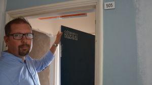 """Patrik Fellman håller i en dörr där det står graverat """"GÖTEBORGS HÖGSKOLAS STUDENTKÅR"""""""