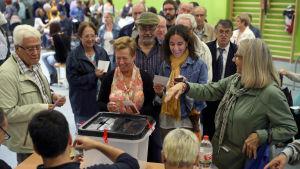 Glada katalaner lägger sina röster i valurnan i en av vallokalerna i Barcelona