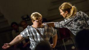 Skådespelare i rutig skjorta koncentrerar sig, en annan har utsträckt hand