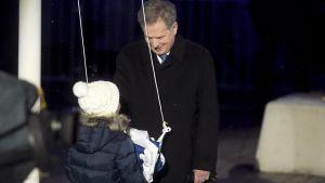 Sauli Niinistö med ett barn som ska dra upp Finlands flagga i flaggstången.