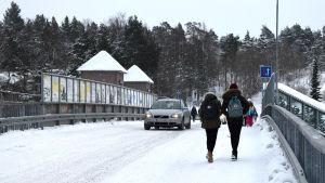 Bilar och fotgängare går på järnvägsbron i Karis en vintrig dag.