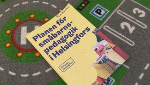 En häftad plan för småbarnspedagogik på en bilmatta.