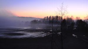 Aurinko nousee peltoaukeman takaa.