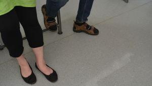 Ett par fötter på ett skolgolv i Karjaan yhteiskoulu i Karis.