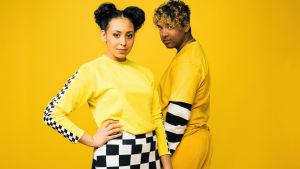 Nuori nainen ja mies katsovat kameraan keltaisella taustalla, keltaisisssa ja mustavalkoisissa vaatteissa.