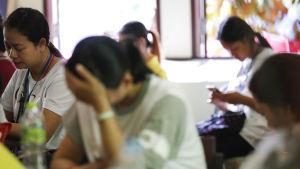 Föräldrar och släktingar till de instängda fotbollspojkarna sitter i ett rum och ser oroade ut.