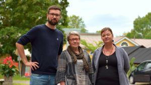 En lång man med mörkt skägg och glasögon och två kvinnor, en med ljust kort hår och glasögon och en med mörkt långt hår utomhus en mulen sommardag. I bakgrunden träd, en träbyggnad och en bil.