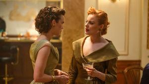 Karaktärerna Nina och Ester tittar på varandra argt under en fest.