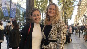 Två kvinnor står på en gata i Paris. De håller varandra om ryggen och ler.