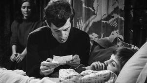 Mies, ilmeisesti pappi, lukee jotakin sängyssä makaavalle pojalle.