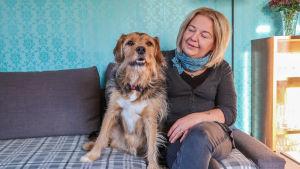En kvinna sitter på en soffa med sin hund.