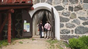 Kaksi ihmistä kurkistaa sisälle Navetan ovesta Vehmaan kartanon tilalla Juvalla.