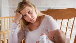 Trött mamma meb baby i famnen