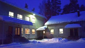 En skolbyggnad täckt av snö. På bilden syns fem olika ingångar till skolan.
