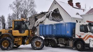 Snöröjning, snö stjälps över på en lastbil.