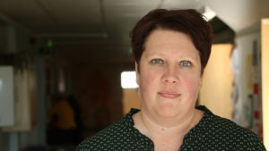 En kvinna med kort mörkt hår står i en mörk korridor.