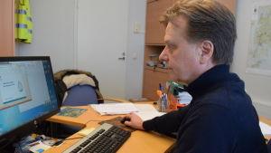 Raimo Parikka sitter vid datorn i sitt kontor.