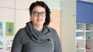 En kvinna med mörkt hår, grå tröja och glasögon. Står inne i ett rum i ett daghem. Inga barn syns.