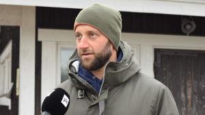 En man i mössa på en brygga. Blir intervjuad. Man kan se lite av en mikrofon.