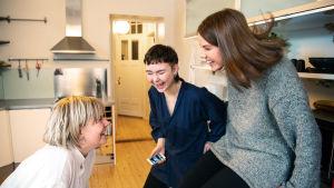 Tre kvinnor skrattar i ett kök. En av dem håller i en telefon.