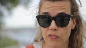 Vit kvinna med ljust hår och solglasögen gör en något skeptisk min med munnen.
