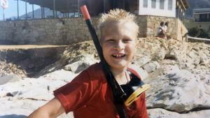 Rapartisten Paleface som liten pojke på semester, har på sig en snorkelutrustning.