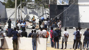 Migranter och myndigheter kring den förstörda hangaren i Tajoura på onsdagen.