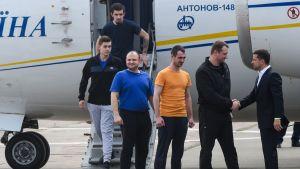 Ukrainas president Volodymyr Zelenskyj (till vänster) tog emot de frigivna ukrainska fångarna då de landade på flygplatsen i Kiev.