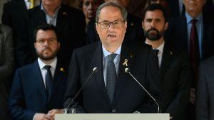 Kataloniens regionpresident Quim Torra håller tal. I bakgrunden ses ett antal män i mörka kostymer, likt den som Quim Torra bär.
