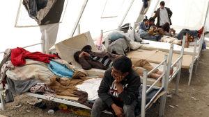 En man sitter på en säng inne i ett tält på ett flyktingläger med flera sängliggande i bakgrunden.