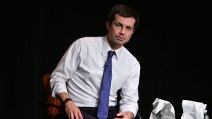 En man i vit skjorta med blå slips sitter på en stol framför kameran.