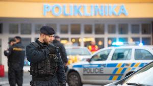 En polis i svarta kläder tittar ner mot sin axel. I bakgrunden finns polisbilar med sirener och ett sjukhus.