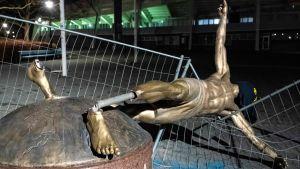 Statyn av Zlatan är avsågad vid fötterna och den lutar mot ett stängsel