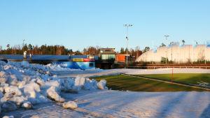 En snöhög till vänster framför grönt gräs och en kupolformad bollhall.