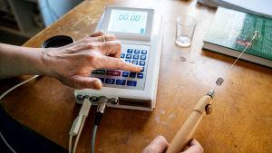 En bioresonansmaskin ligger på ett bord. Den har en kontrollenhet med knappar och en display. I en sladd sitter ett trähandtag med en en antenn på.